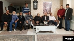 Family and friends of Pooya Bakhtiari. Father and mother sitting on right side sofa, father in white shirt. Grandfather in blue-striped shirt (L). Undated
