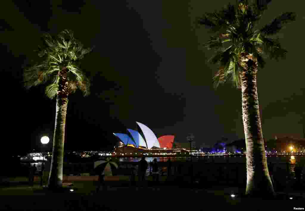 The blue, white, and red colors of France's national flag are projected onto the sails of Sydney's Opera House in Australia as a show of solidarity with the people of France following the November 13 terrorist attacks in Paris. (Reuters/Jason Reed)