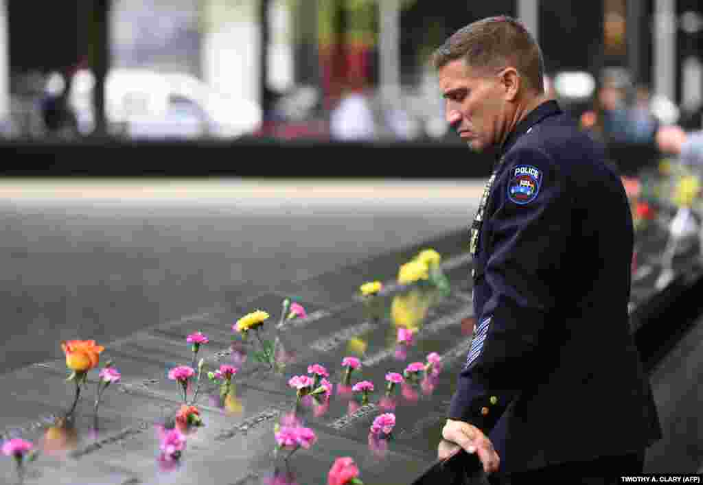 A Port Authority police officer looks down into the South Pool during observances on September 11 held on the 17th anniversary of the September 11, 2001, terror attacks at the annual ceremony at the Ground Zero memorial site in New York City. (AFP/Timothy A. Clary)