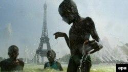 Французские дети, спасающиеся от жары в фонтане.