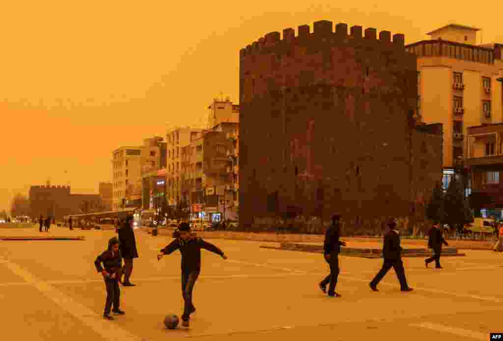 Boys play football during a dust storm in the Turkish town of Diyarbakir on April 9. (AFP/Ilyas Akengin)