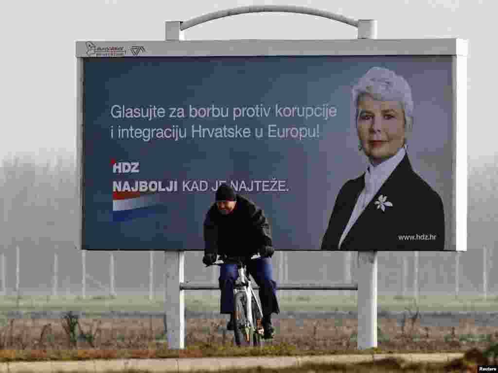 A man rides past a billboard for Croatia's ruling HDZ party, led by Prime Minister Jadranka Kosor, near Zagreb airport on November 28. (REUTERS/Nikola Solic)