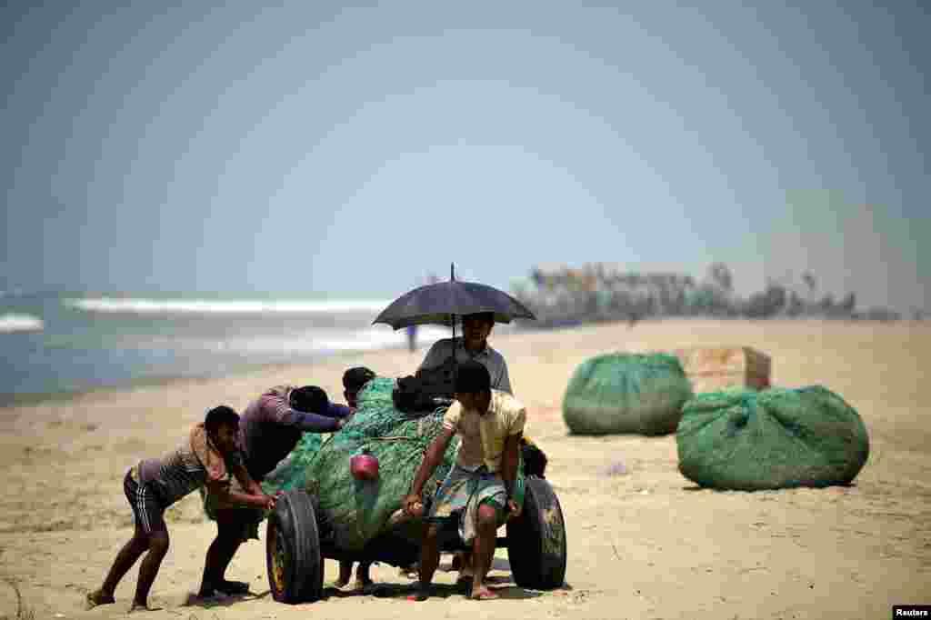 Беженцы на побережье толкают повозку груженную новым уловом. 11 июня 2018 года.