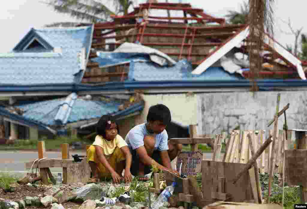 Romualdo Redona and his younger sister Angel offer prayers and candles at the grave of their siblings who were killed by supertyphoon Haiyan a month ago and buried in a vacant lot along a main road in Tanuan, in the Philippines' Leyte province. (Reuters/Romeo Ranoco)
