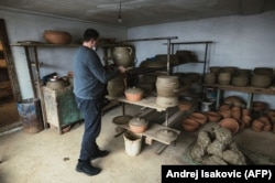 Goran Savic places a pot to dry before it is baked.