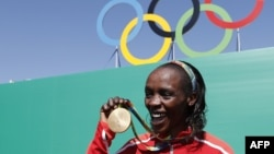 Kenyan gold-medalist Jemima Jelagat Sumgong poses after the podium ceremony for the women's marathon at the Rio 2016 Olympic Games at Sambodromo in Rio de Janeiro on August 14.