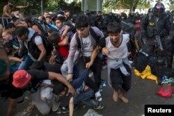 Мигранты бегут во время стычки с полицией Венгрии на границе с Сербией. 16 сентября 2015 года.