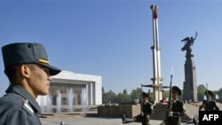 Kyrgyzstan -- Honor guards march near a national flag standing at half -mast in Bishkek, 07Oct2008