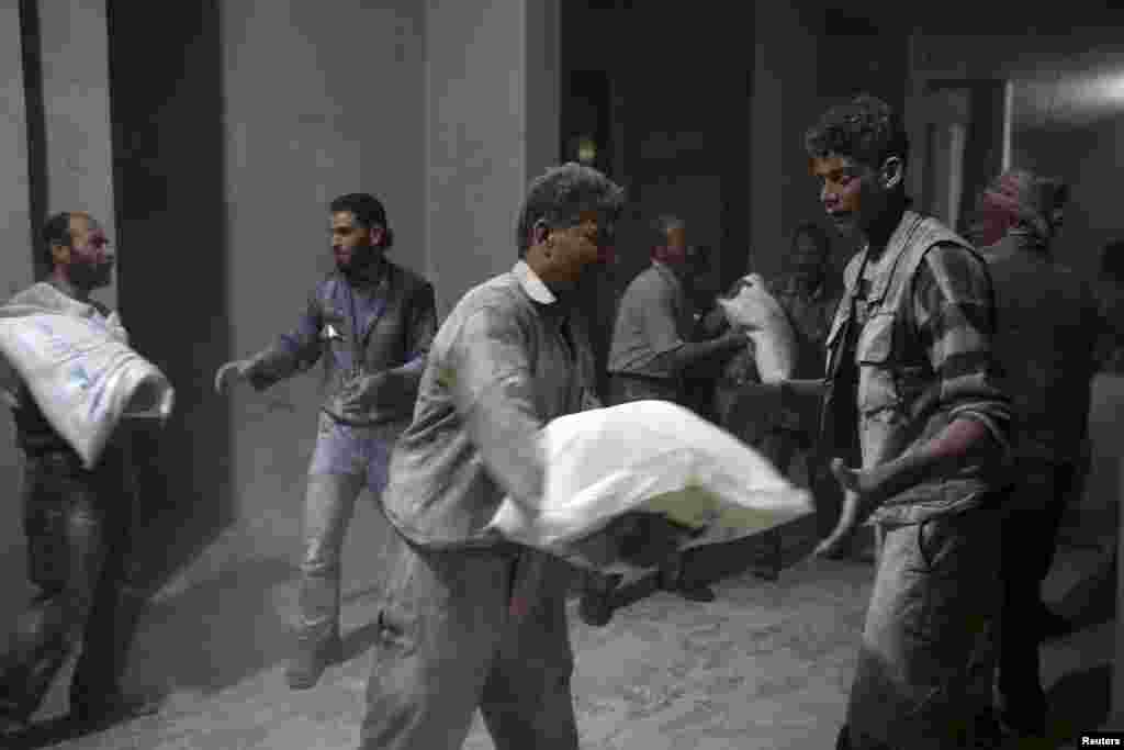 Men unload bags of flour from a Red Crescent aid convoy in the besieged, rebel-held town of Jesreen, in the eastern Damascus suburb of Ghouta, Syria. (Reuters/Bassam Khabieh)