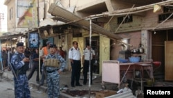 رجال أمن يتفحصون موقع إنفجار بالمسيّب