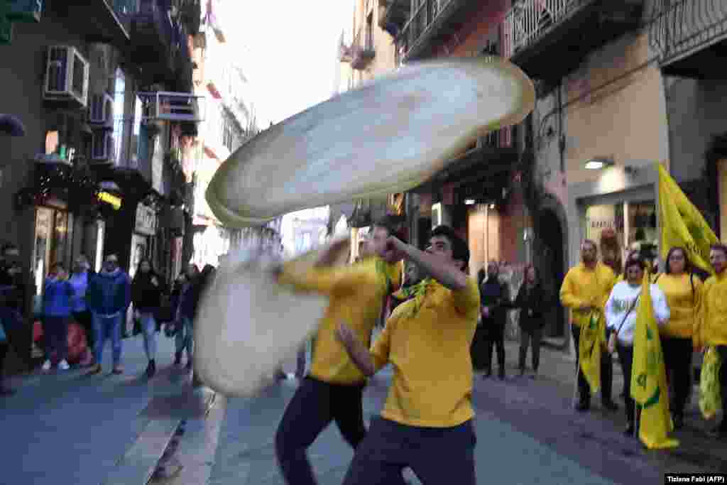 "In Naples, members of the Pizzaioli Acrobats Coldiretti celebrate a decision by UNESCO to make the art of Neapolitan ""Pizzaiuolo"" an ""intangible heritage."" The art of the Neapolitan ""Pizzaiuolo"" is a culinary practice consisting of four different phases relating to the preparation of the dough and its baking in a wood-fired oven. The practice originates in Naples, where around 3,000 Pizzaiuoli now live and perform. (AFP/Tiziana Fabi)"