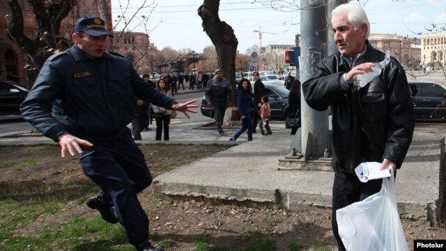 Armenia - A policeman rushes to stop a man from setting himself on fire, Yerevan, 7Mar2014.