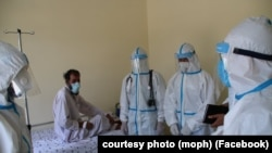 FILE: Healthcare workers treat a person infected with the coronavirus in the eastern Afghan province of Laghman in June.