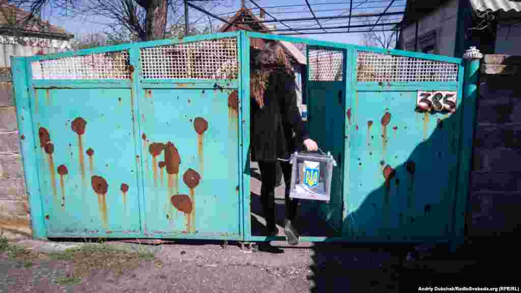 An election official brings a ballot box to the front-line village of Novotroitse in the Donetsk region on April 21. As the gates show, most homes here have been damaged by shelling.