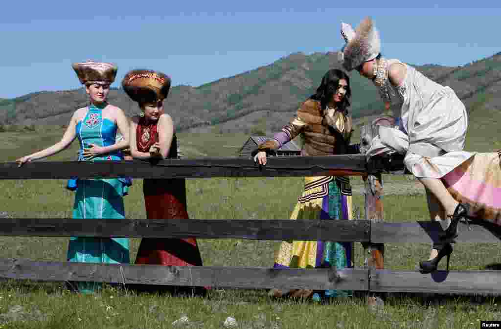 Models of the Altyr fashion theater, dressed in Khakas national costumes, climb over a wooden fence during a photo session, as part of the rehearsal for the Tun-Pairam traditional holiday (The Holiday of the First Milk) celebration at a museum preserve outside the village of Kazanovka near Abakan in the Republic of Khakassia, Russia. (Reuters/Ilya Naymushin )