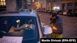 یک رضاکار در حال توزیع ماسک صورت ساخته شده در خانه برای مردم در شهر پراگ پایتخت جمهوری چک. March 17, 2020