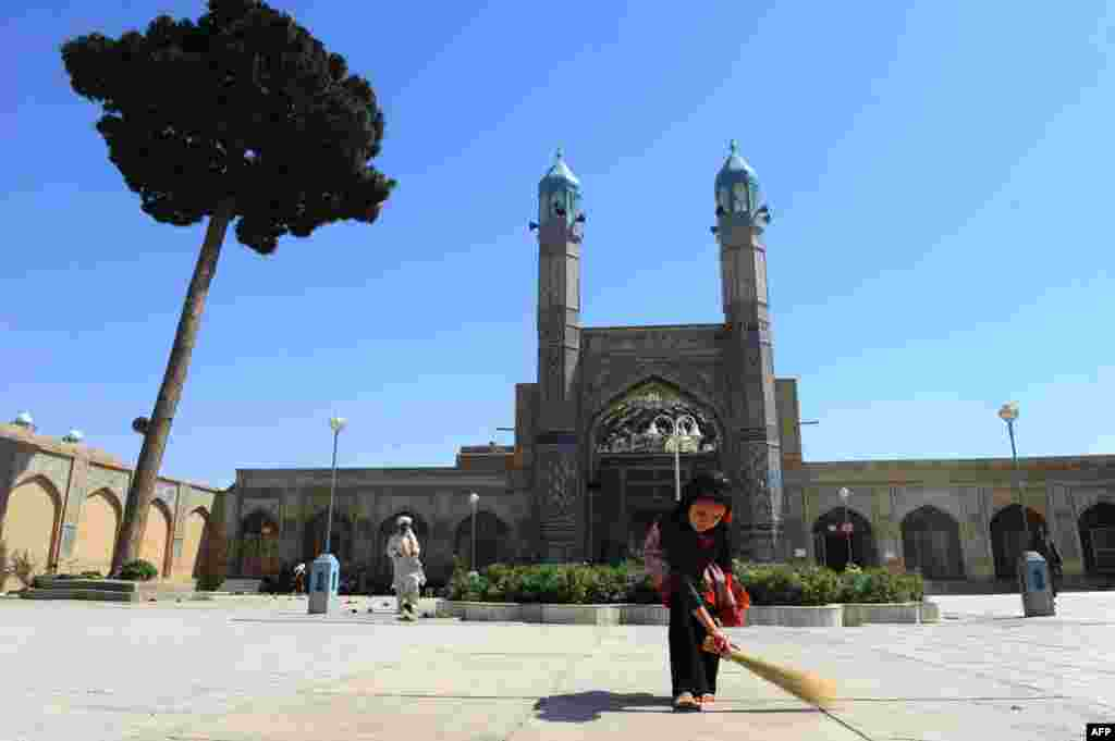 An Afghan girl sweeps at the main mosque in Herat ahead of the Islamic holy month of Ramadan. (AFP/Aref Karimi)