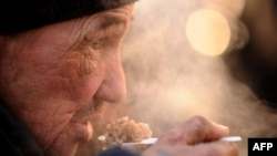 A homeless man eats hot food given out by the Emergency Situations Ministry in Moscow.