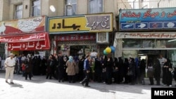 Iranians wait to buy chicken outside a butcher shop in Shiraz in July.