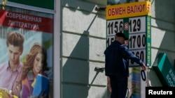 Сотрудники обменного пункта меняют цифры на табло с курсами валют. Одесса, 7 мая 2014 года.