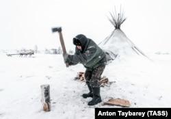 Ненецкий автономный округ. Оленевод рубит дрова для печи