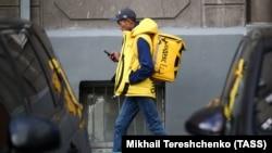 """МОСКВА - Сотрудник сервиса по доставке еды """"Яндекс Еда"""" на одной из улиц города."""