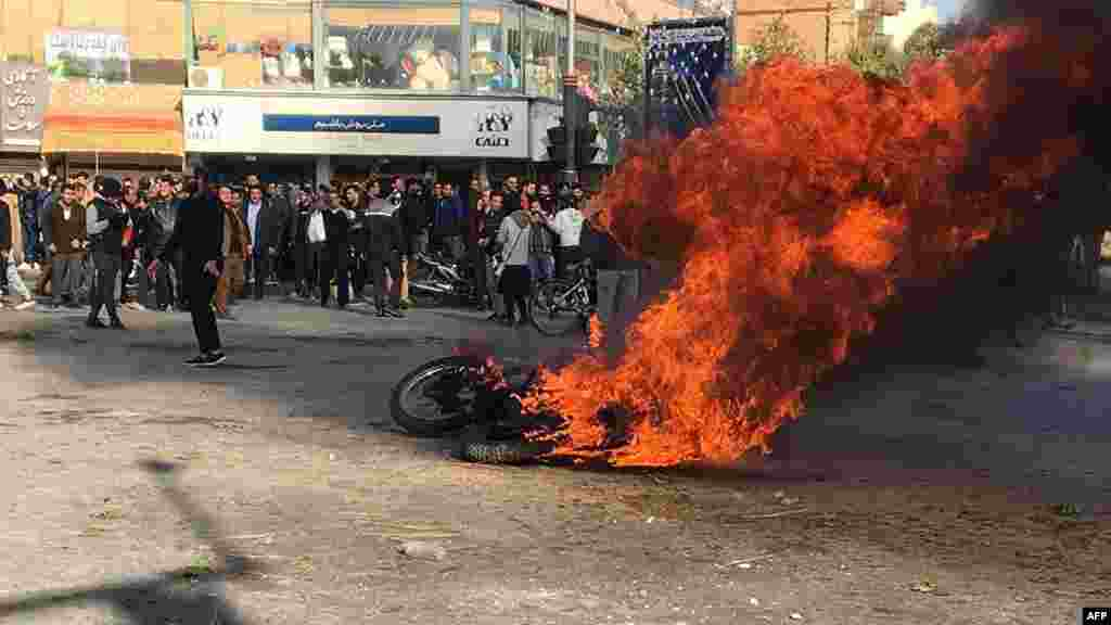 Iranian protesters gather around a burning motorcycle during a demonstration against an increase in gasoline prices in the central city of Isfahan on November 16. (AFP)