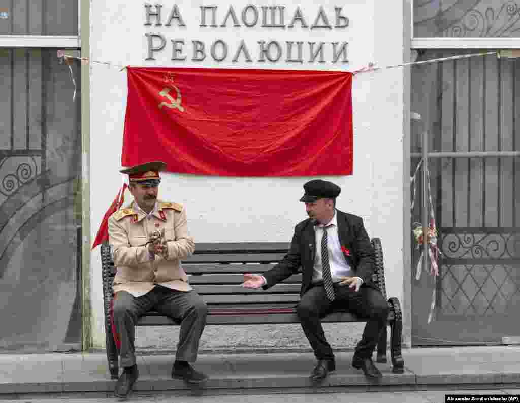 Two men impersonating Soviet founder Vladimir Lenin (right) and Soviet leader Josef Stalin talk to each other while waiting to pose with tourists in Moscow. (AP/Aleksandr Zemlyanichenko)