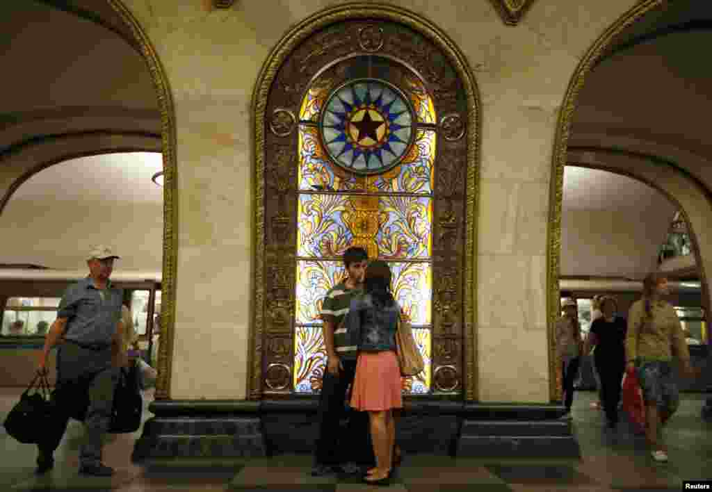 A couple kisses in front of a stained-glass panel at the Novoslobodskaya metro station, which was built in 1952.