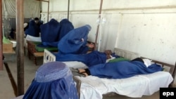 Schoolgirls receive first aid after inhaling a mysterious poisonous gas in Takhar in late May.