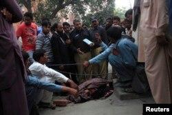 Таспен ұрып өлтірілген Фарзананың денесінің жанында айғақ жинап жүрген полицейлер. Пәкістан, Лахор, 27 мамыр 2014 жыл.