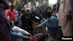 Police collect evidence near the body of Farzana Parveen, who was stoned to death by her relatives in Lahore on May 27.