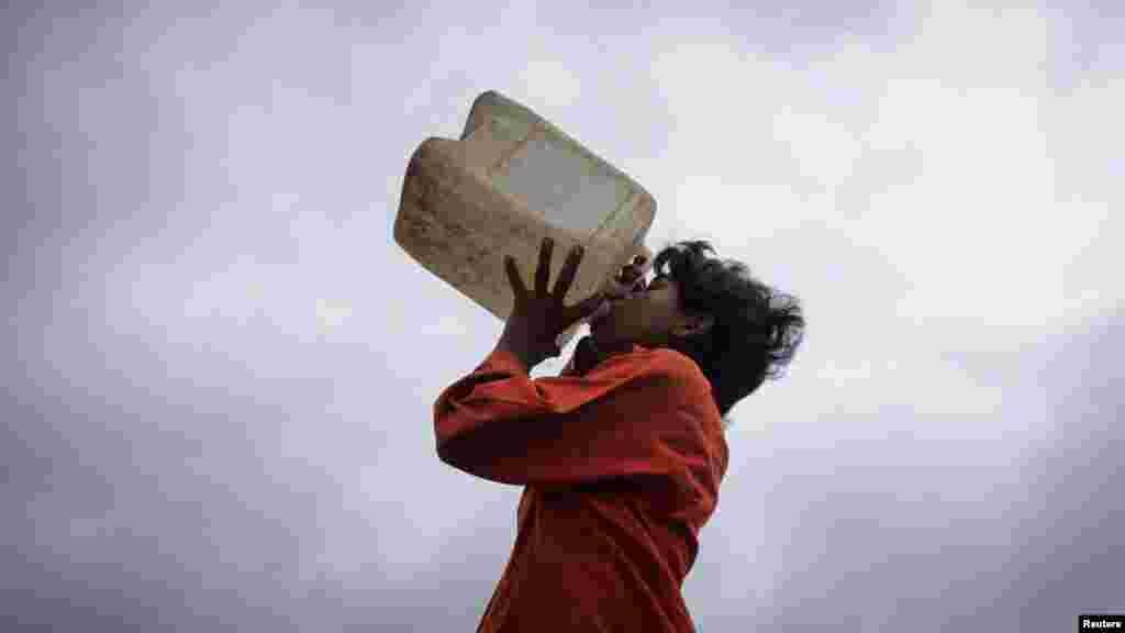 A boy drinks water from a plastic container in Karachi, Pakistan.