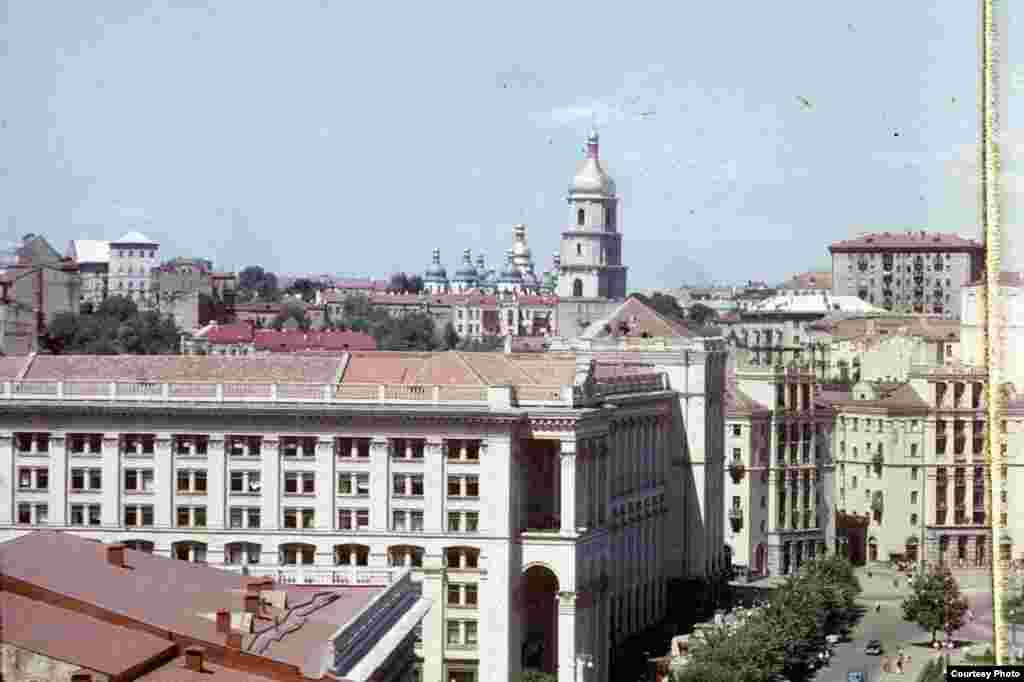 In this photograph of Kyiv, one can see where central Khreshchatyk Street runs through Independence Square. The large building on the corner is the Main Post Office, with St. Sophia's Cathedral and its belfry in the background.