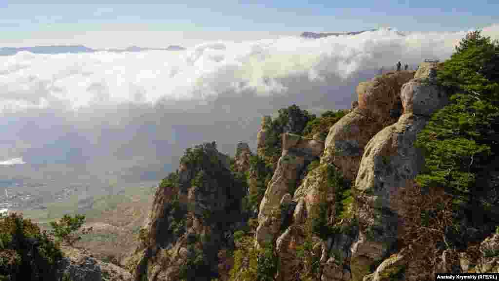 Bulutlarnıñ artından Çatır Dağnıñ töpeleri körüne