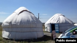 Автомобиль рядом с казахской юртой в степи.