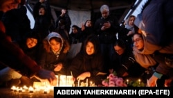 Iranians light candles for victims of the downed flight in Tehran on January 11.