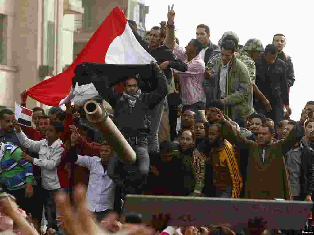 Demonstrators celebrate atop an army tank in Tahrir Square during protests in Cairo on January 29.