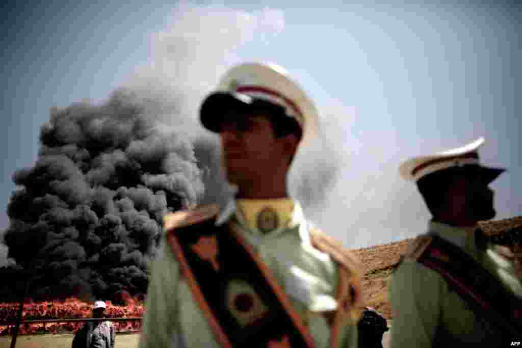 Policemen stand guard as the contraband is incinerated.