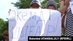 """Дети с плакатом: """"Отпустите моего отца!"""" у акимата Жанаозена во время визита в город преьмьер-министра Карима Масимова, июль 2012 года."""