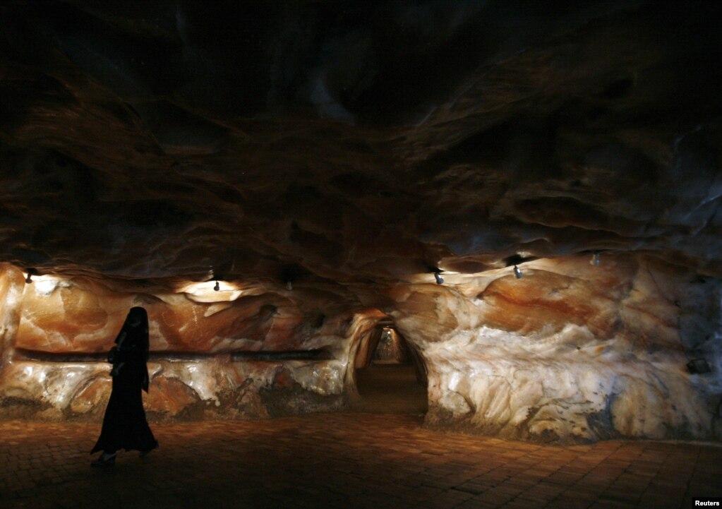 Một người phụ nữ mặc một chiếc burqa màu đen đi qua các mỏ muối của Khewra.