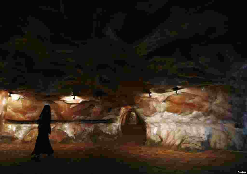 A woman dressed in a black burqa walks through the salt mines of Khewra.