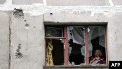 Жінка у зруйнованій внаслідок бойових дій будівлі, Луганськ, липень 2014 року