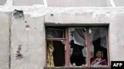 Një banore shihet në dritaren e shtëpisë së saj e cila ishte dëmtuar nga predhat e forcave të qeverisë së Ukrainës në pjesën lindore të Ukrainës