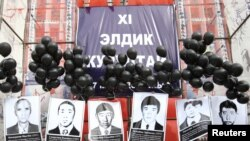 Mourners last year hold portraits of the people killed by policemen during the Aksy protests in 2002.