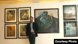 الفنان قيس السندي أمام لوحاته في معرضه (الفردوس المفقود)