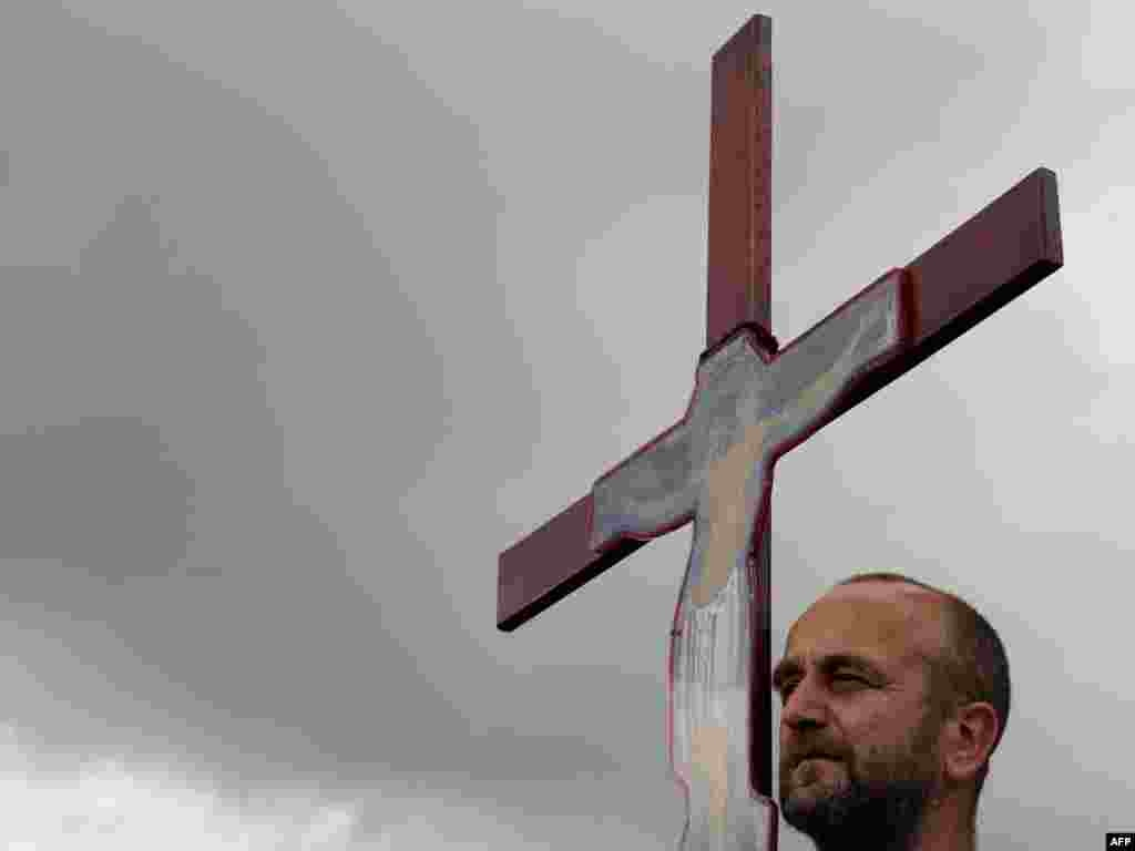 A Kosovo Serb holds up a cross during a ceremony at Gazimestan, near Pristina, on June 28. The ceremony marked the anniversary of the 1389 Battle of Kosovo, in which the Ottoman Empire defeated the Serbian army. Photo by Armend Nimani for AFP