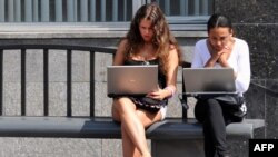 Teenage girls work on laptop computers while wating for a public bus in Moscow. After decades of of foreign travel, imported goods, and access to the Internet, it remains to be seen if ordinary Russians would welcome being cut off from the rest of the world.
