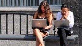 Девушки сидят с ноутбуками на автобусной остановке в Москве.