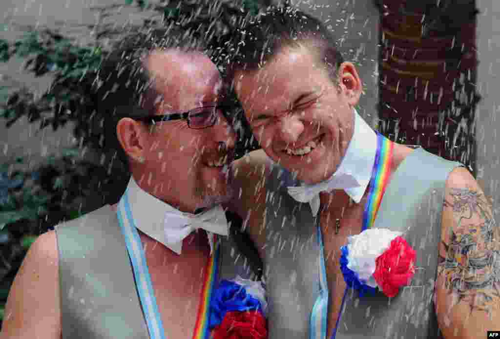Russians Aleksandr Emereev (left) and Dmitry Zaytsev smile after getting married in Buenos Aires, Argentina, on February 25.Alexander and Dmitry married in Buenos Aires for fear of homophobia in their country. (AFP/Daniel Garcia)